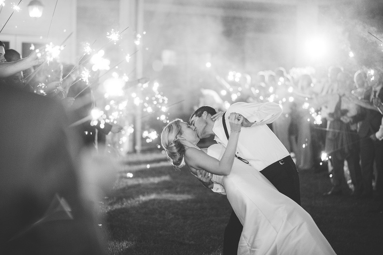 black and white groom dipping bride sparkler send off